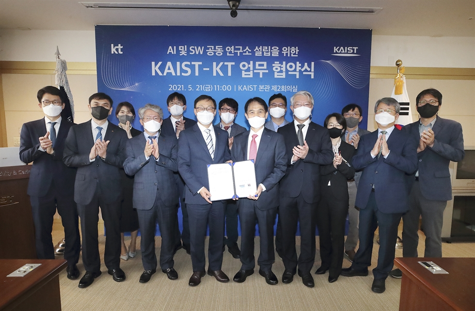 KT CEO Ku Hyeon-mo, left, and Korea Advanced Institute of Science and Technology (KAIST) President Lee Kwang-hyung, pose after signing an agreement to jointly set up a research institute for artificial intelligence (AI) and software development, at the KAIST main campus in Daejeon, Sunday. Courtesy of KT
