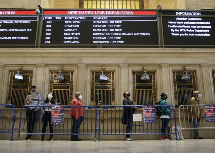 People stand in line near ticket booths to receive COVID-19 vaccine injections at a pop-up vaccine center at New York City's Grand Central Terminal, last week. UPI-Yonhap