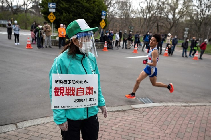 A volunteer holds a placard asking the people on the street to refrain from watching the event to prevent the spread of COVID-19 while an athlete competes in the half-marathon race, a test event for the 2020 Tokyo Olympics, in Sapporo, Japan, May 5. AFP-Yonhap