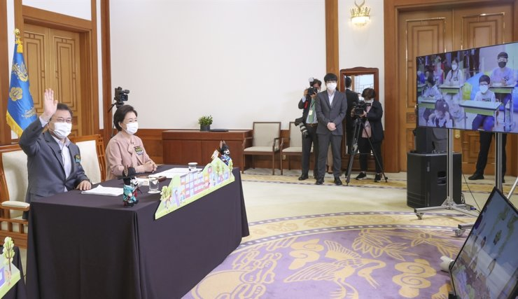 President Moon Jae-in and his wife Kim Jung-sook smile during an online meeting with a group of elementary school students, at Cheong Wa Dae, May 5 (Children's Day). Yonhap