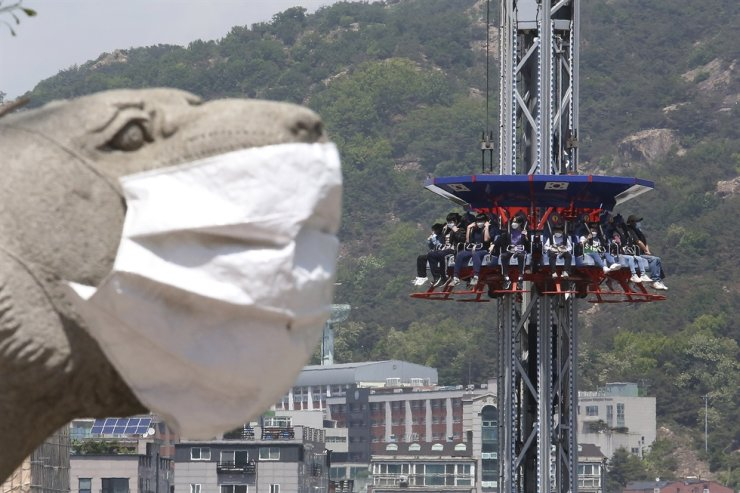People wearing face masks as a precaution against the coronavirus ride Gyro Drop as they visit to celebrate Children's Day at Children's Grand Park in Seoul, May 5. AP-Yonhap