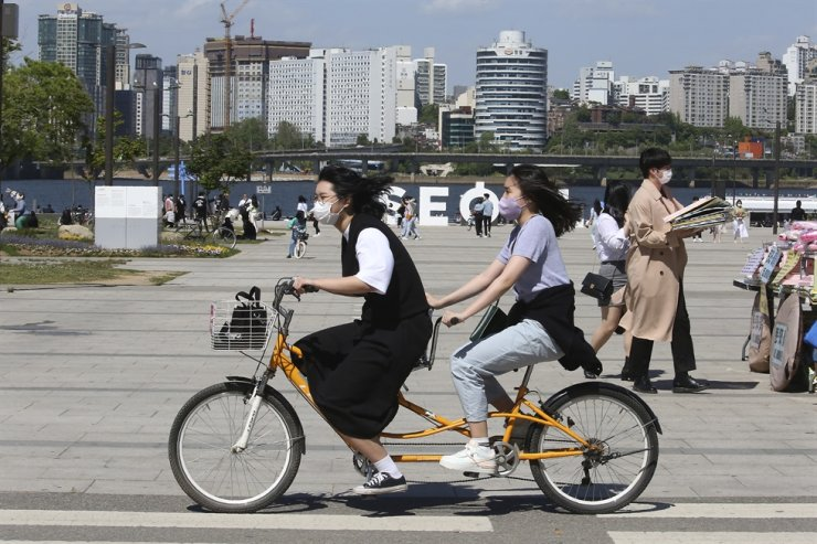 Women wearing face masks as a precaution against the coronavirus ride a bicycle at a public park along the Han River in Seoul, May 9. AP-Yonhap