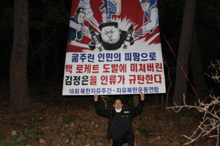Park Sang-hak, head of a North Korea defectors' activist group, Fighters for a Free North Korea, holds a placard criticizing the North's leader Kim Jong-un in this undated handout photo. The group said Friday that it had flown balloons containing leaflets and booklets condemning Kim into the country twice between April 25 and 29. Courtesy of Fighters for a Free North Korea