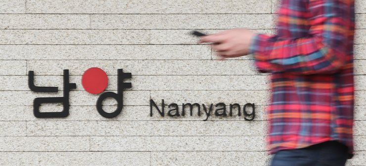 A pedestrian passes by Namyang Dairy Products headquarters building in Seoul, Friday. Yonhap