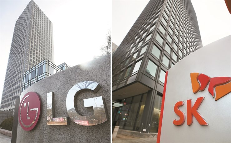 Company logos of LG and SK are seen in front of their respective corporate headquarters in Seoul. Korea Times file