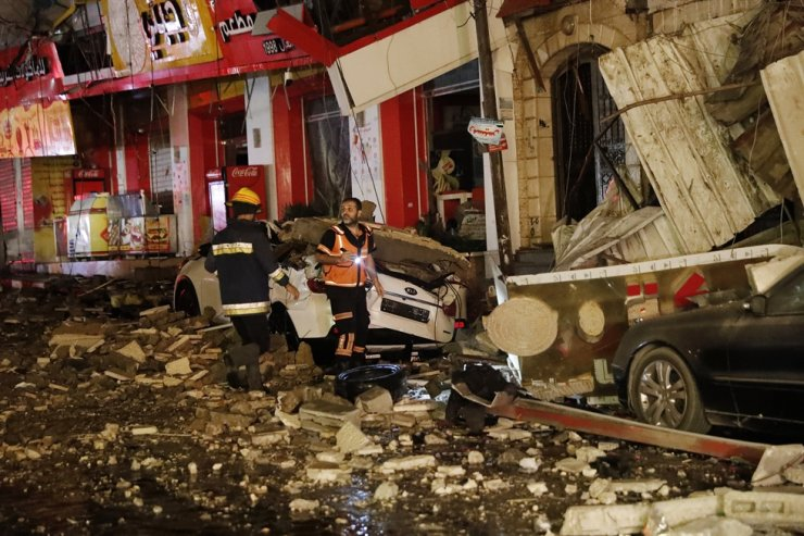 Firefighters inspect destroyed buildings after it was hit by Israeli airstrikes, Gaza City, May 12. AP-Yonhap