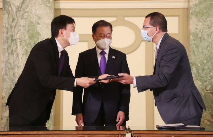 President Moon Jae-in, center, poses with Samsung Biologics CEO John Rim, left and Moderna CEO Stephane Bancel during a vaccine partnership event held between Korea and the United States at a hotel in Washington, D.C., May 22. Yonhap