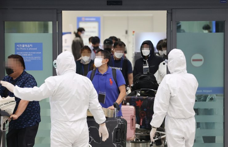 Koreans who flew from India via a chartered flight come out of arrivals' gate inside Incheon International Airport, Friday, as health officials guide them to where they can take coronavirus tests. Yonhap