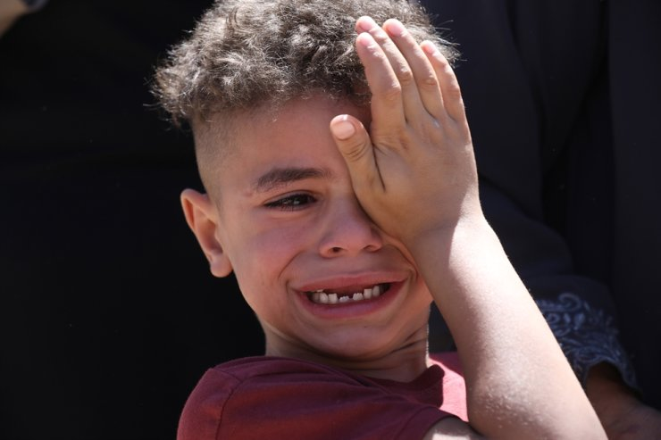 A boy cries during the funeral of Palestinian Malik Hamdan, who was killed during clashes with Israeli troops, during his funeral in the West Bank village of Salem near Nablus, May 15, 2021. EPA