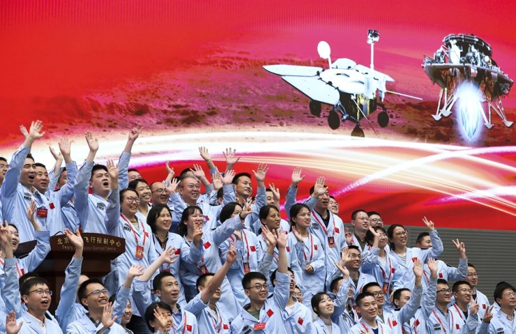 Scientists and engineers of the Beijing Aerospace Control Center celebrate after China's Tianwen-1 probe successfully landed on Mars, May 15, in this photo released by Xinhua News Agency. AP