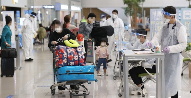 Quarantine officials guide entrants from overseas at Terminal 2 of Incheon International Airport, Wednesday. Yonhap