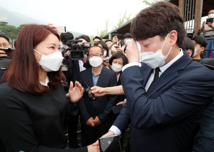 Lee Jun-seok, right, the new chairman of the main opposition People Power Party (PPP), sheds tears while talking with a bereaved family member of the 2010 sinking accident of ROK naval ship of Cheonan, during his visit to the Daejeon National Cemetery, Monday. Lee started his first official schedule as the party leader by visiting the national cemetery, three days after his election at the party convention. Yonhap