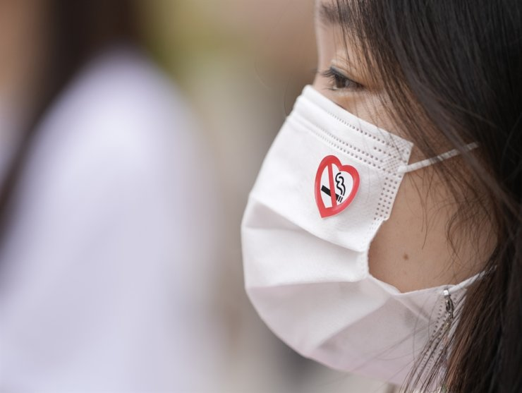 An activist wearing a face mask as a precaution against the coronavirus with no-smoking sign attends at a campaign on a street to mark World No Tobacco Day in Seoul, May 31. AP-Yonhap