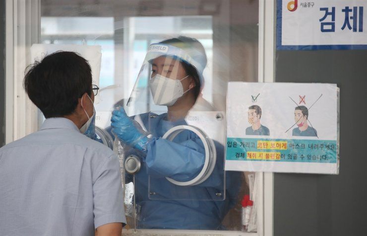 A medical worker takes samples for COVID-19 at a makeshift testing center near Seoul Station in Seoul, June 23. Yonhap