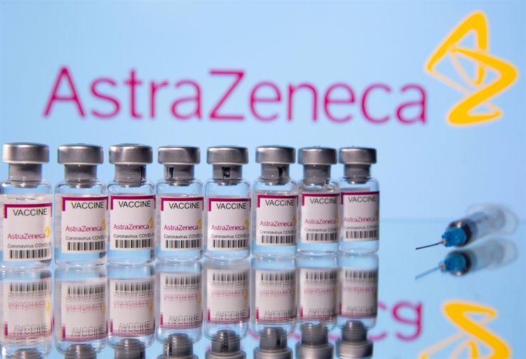 Vials labelled 'Astra Zeneca COVID-19 Coronavirus Vaccine' and a syringe are seen in front of a displayed AstraZeneca logo, in this illustration photo taken March 14. Reuters-Yonhap