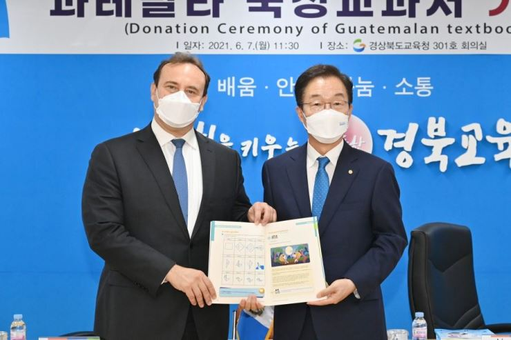 Lim Jong-sik, right, superintendent of the Gyeongsangbuk-do Office of Education, and Guatemalan Ambassador to Korea Marco Tulio Chicas Sosa, hold a textbook for elementary school students in Guatemala, at Lim's office in Andong, North Gyeongsang Province, June 7. Courtesy of Gyeongsangbuk-do Office of Education