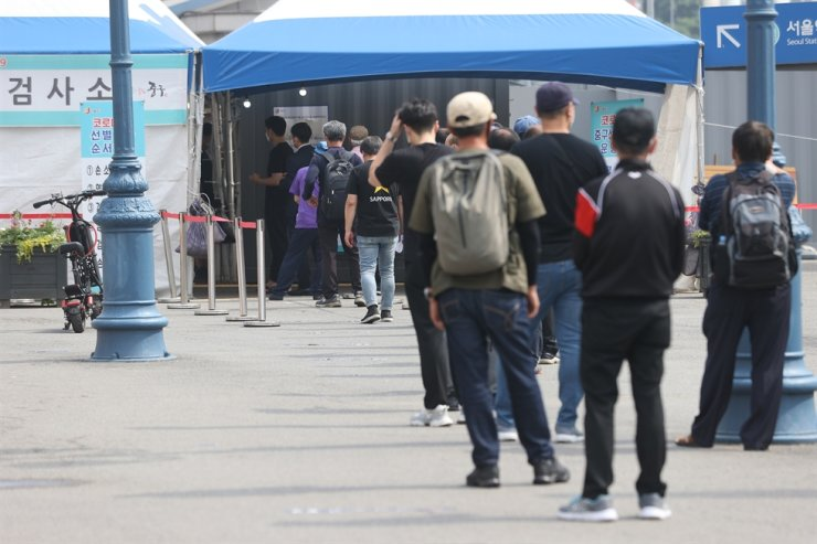 People stand in line at a temporary COVID-19 testing center set up in Seoul Station, June 6. Yonhap