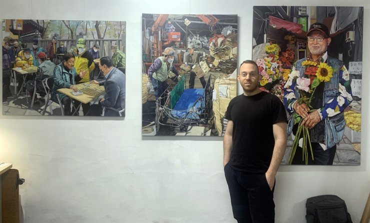 Aaron Cossrow poses with some of his art. / Courtesy of Kyung Lee
