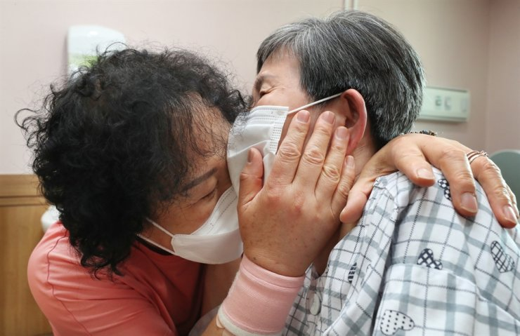 A mother, right, who has been at a geriatric hospital in Daejeon, and her daughter meet in person, Tuesday, for the first time since March 20 last year when the authorities banned in-person meetings between patients at such facilities and their families to prevent COVID-19 infection among patients. They began to allow the meetings if either the patient or the family member has been fully vaccinated. Yonhap