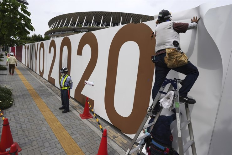 Workers paste the overlay on the wall of the National Stadium, where opening ceremony and many other events are scheduled for the postponed Tokyo 2020 Olympics, June 2, in Tokyo. Korea is not considering boycotting the Tokyo Olympics, the foreign ministry said June 8, AP-Yonhap
