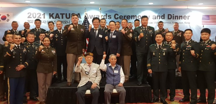 Choi Kyoo-ok, standing front row center on the podium, chairman of Osstem Implant, poses with Eighth U.S. Army Commanding General Lt. Gen. Bill Burleson, standing front row left on the podium; Kim Hae-sung, chairman of the KATUSA Veterans Association, standing front row right on the podium; and Korean and U.S. service personnel and other guests during the KATUSA Awards Ceremony and Dinner at U.S. Army Garrison Humphreys in Pyeongtaek, Gyeonggi Province, June 16. Courtesy of Osstem Implant