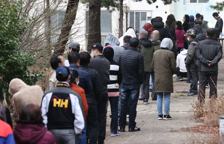 People wait in long lines for COVID-19 tests at a separate temporary testing facility for foreign nationals in front of the Geumcheon District Office in Seoul, March 21. Yonhap