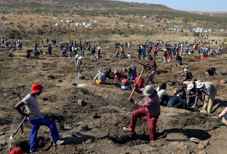 A man uses a pickaxe to dig as fortune seekers flock to the village after pictures and videos were shared on social media to show people celebrating after finding what they believe to be diamonds, in the village of KwaHlathi outside Ladysmith, South Africa, June 14. Reuters-Yonhap