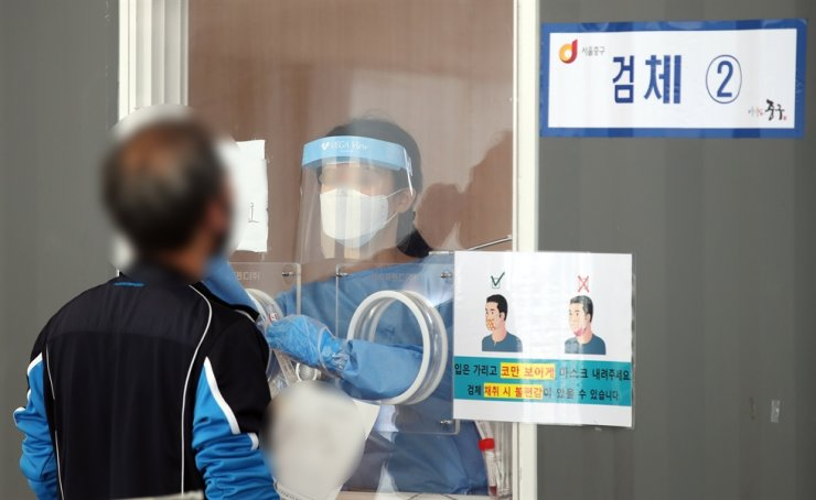 A man gets a COVID-19 testing at a makeshift testing site near Seoul Station, June 5. Yonhap