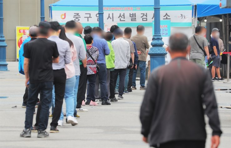 People wait in a line to go through COVID-19 testing at a makeshift testing center in Seoul, June 7. Yonhap