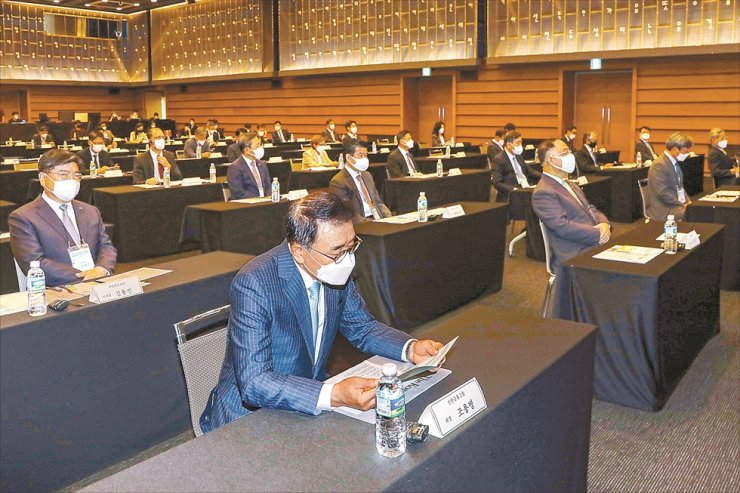 Shinhan Financial Group Chairman Cho Yong-byoung reads the program during the 2021 Korea Times Global ESG Forum. Korea Times photo by Shim Hyun-chul
