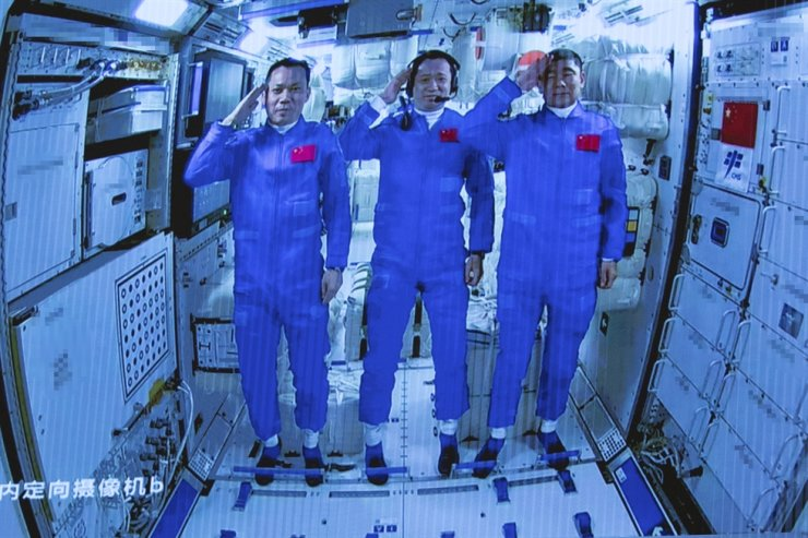 In this photo released by Xinhua News Agency, Chinese astronauts salute after successfully entering the Tianhe space station module as they are displayed on a big screen at the Beijing Aerospace Control Center in Beijing, June 17. AP-Yonhap