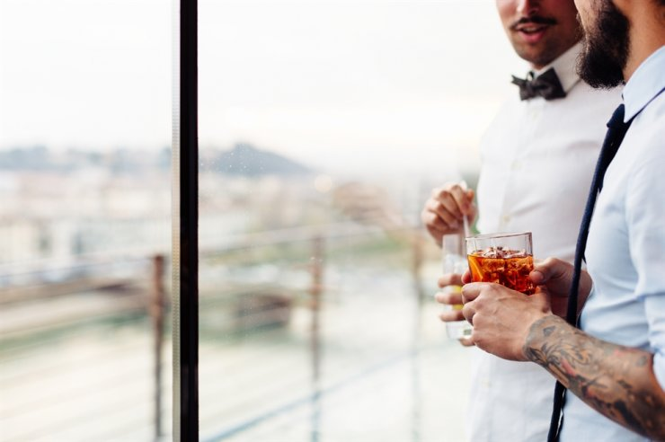 Two man drink Negronis, the signature cocktail of Italy. Courtesy of Booking.com