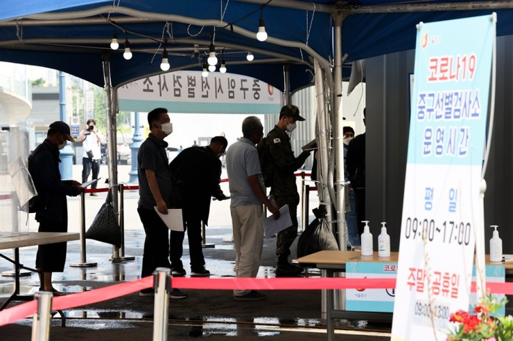 People wait to get tested for COVID-19 at a testing center in Seoul Station, June 20. Yonhap