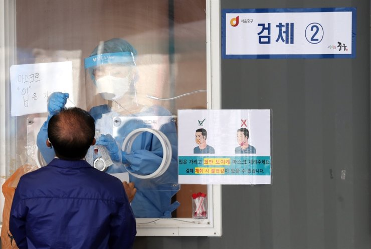 A medical worker takes samples for COVID-19 at a makeshift testing center near Seoul Station in central Seoul, June 1. Yonhap