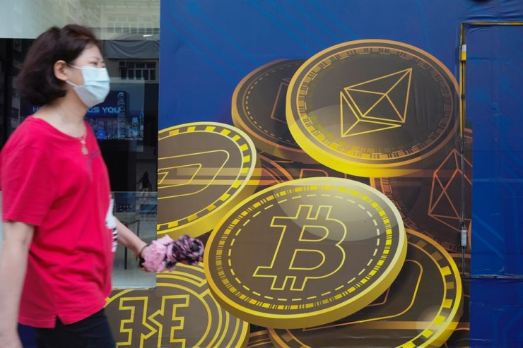 In this June 1 file photo, a woman walks past an advertisement for the Bitcoin cryptocurrency in Hong Kong. Bitcoin fell as low as $31,333, a two-week trough, dragging down other cryptocurrencies. AP-Yonhap