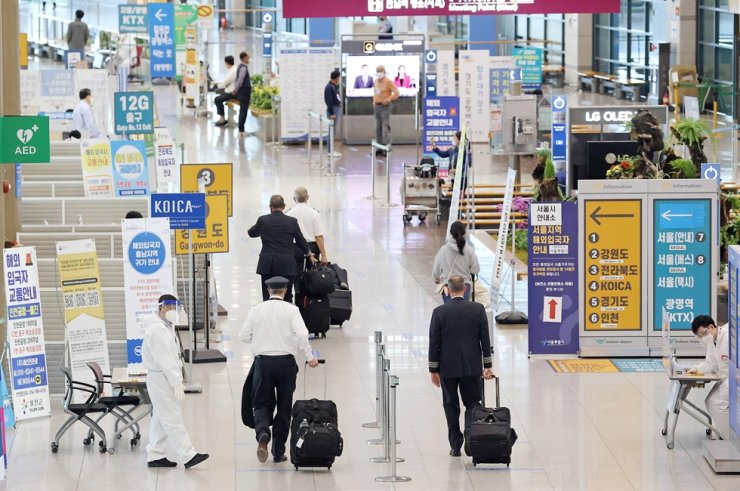 Quarantine officials guide people at the arrival hall of Incheon International Airport, April 21. Yonhap