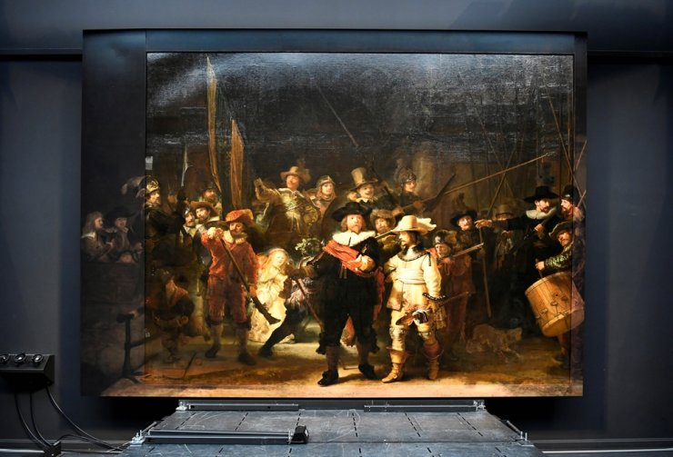 Rembrandt's famed 'Night Watch' is seen back on display for the first time in 300 years, in what researchers say is its original size, with missing parts temporarily restored in an exhibition aided by artificial intelligence at Rijksmuseum in Amsterdam, June 23. Reuters-Yonhap