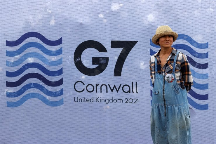 A pedestrian poses for a photograph with a G7 logo outside the media center at Falmouth, Cornwall, June 10. AFP-Yonhap