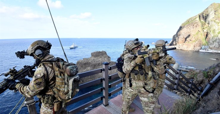 In this Aug. 25, 2019, file photo, members of Korea's Naval Special Warfare Flotilla, also known as SEAL/UDT, stand guard on Dokdo islands during a defense drill on the country's easternmost lands and waters. Courtesy of Republic of Korea Navy
