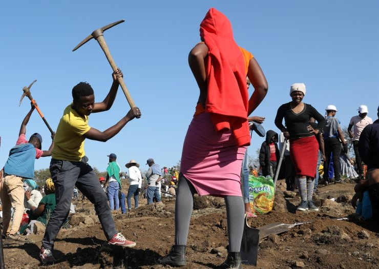 A person uses a pickaxe to dig as fortune seekers flock to the village after pictures and videos on social media showed people celebrating after finding what they believed to be diamonds, in the village of KwaHlathi, South Africa, June 14. Reuters-Yonhap