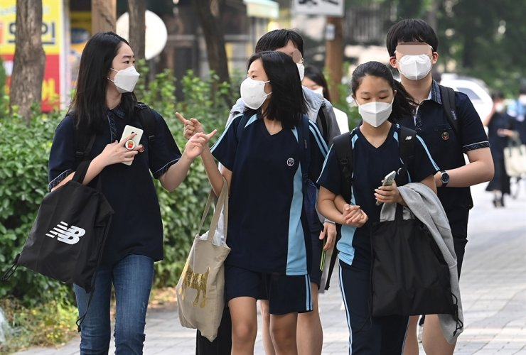 Students of Wolchon Middle School in Seoul's Yangcheon District speak to each other while going to school together, Monday, as the Ministry of Education allowed more students to take part in in-person classes ahead of its plan to fully resume in-person classes from the fall semester. Yonhap
