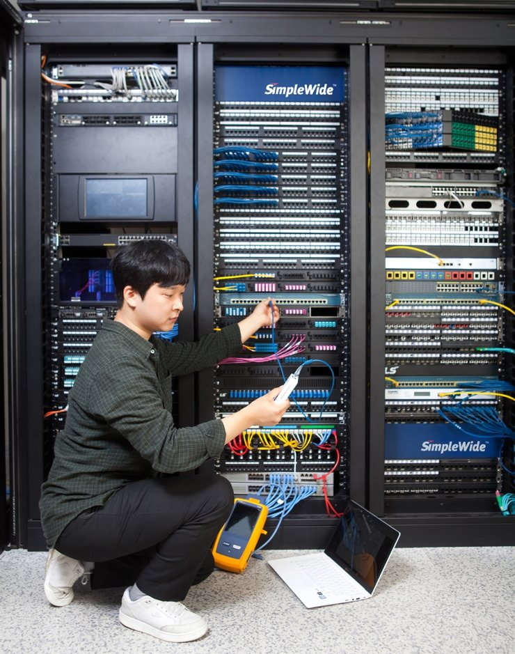 A worker uses LS C&S's new SimpleWide PoE wire for the computerizing system at the firm's headquarters in Anyang, Gyeonggi Province, June 8. Courtesy of LS C&S