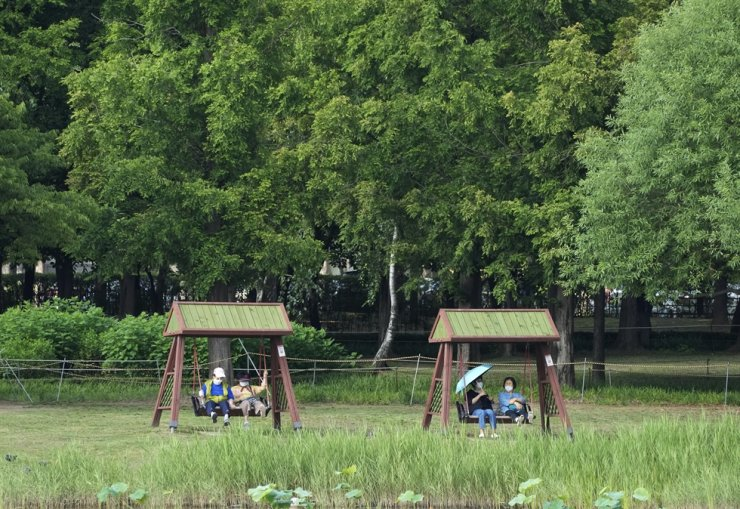 People wearing face masks to help protect against the spread of the coronavirus sit on swings at a park in Goyang, June 15. AP-Yonhap