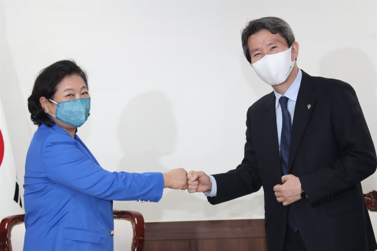 Unification Minister Lee In-young, right, bumps fists with Hyundai Group Chairwoman Hyun Jeong-eun during their meeting at the ministry in Seoul, June 1. Yonhap
