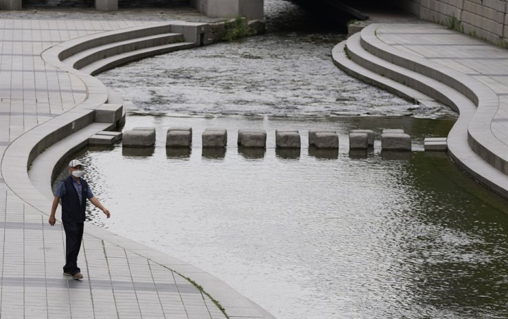 A visitor wearing a face mask as a precaution against the coronavirus walks along a stream in Seoul, June 3. AP-Yonhap