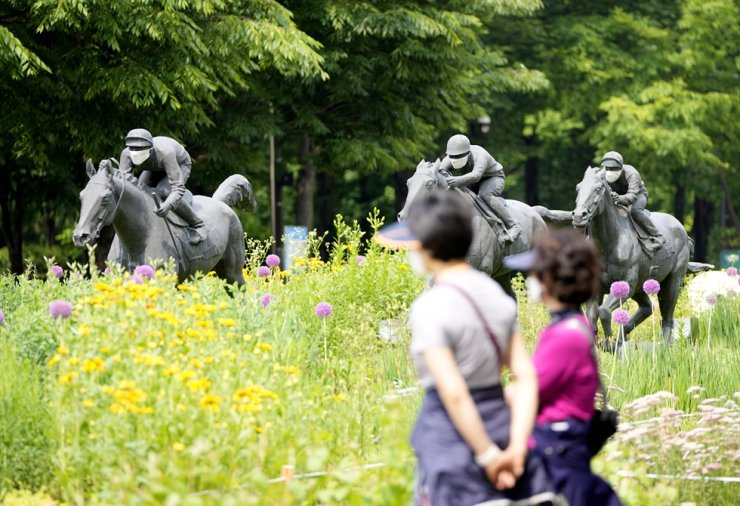 Visitors wearing face masks as a precaution against the coronavirus walk near the sculptures of the horses and riders with masks at a park in Seoul, June 1. AP-Yonhap
