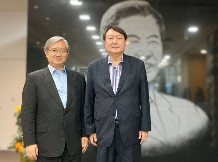 Former Prosecutor General Yoon Seok-youl, right, poses for a photo with Kim Sung-jae, the executive director of the Kim Dae-jung Peace Center, during his visit to the memorial center for former President Kim in Mapo District, Seoul, June 11. Yonhap