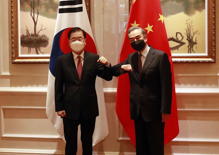 Foreign Minister Chung Eui-yong, left, bumps elbows with his Chinese counterpart, Wang Yi, before their talk in Xiamen, China, April 3. Yonhap