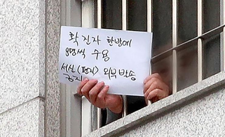 An inmate infected with COVID-19 holds up a message, which reads that eight patients are confined to a single cell, through a window at Seoul Dongbu Detention Center in eastern Seoul in this Dec. 29, 2020 photo. Korea Times photo by Seo Jae-hoon