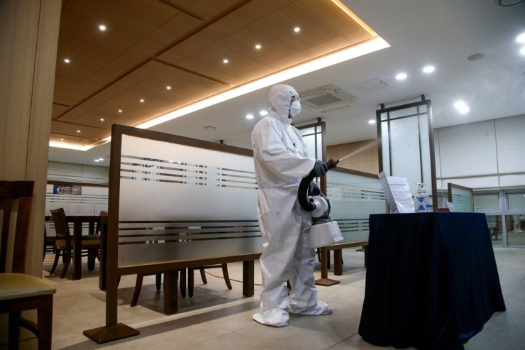 A worker disinfects a public facility at the National Assembly in Seoul, June 11, after an aide of the ruling Democratic Party Chairman Song Young-gil was confirmed to have COVID-19. Yonhap